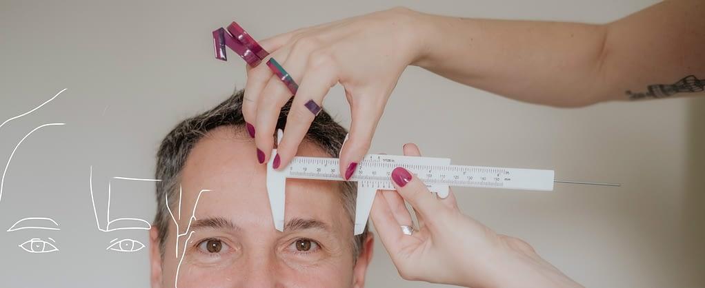 Joice Rossi fazendo análise facial masculina na consultoria de visagismo com paquímetro